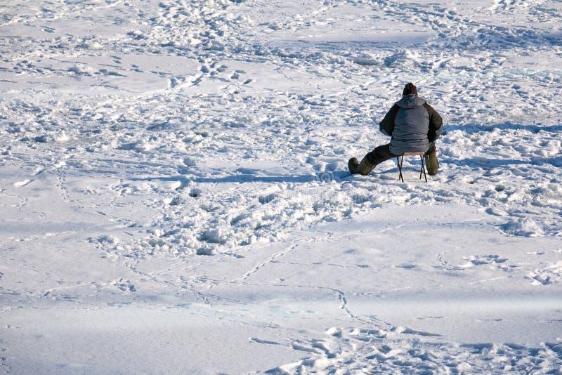 坐在冻湖中间的渔夫等待鱼 免版税库存图片