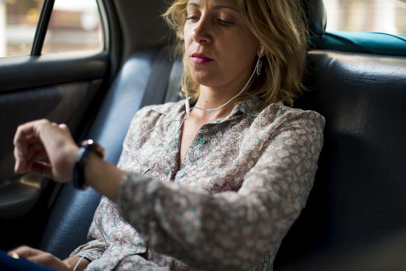 坐在出租汽车的白肤金发的妇女 免版税库存照片