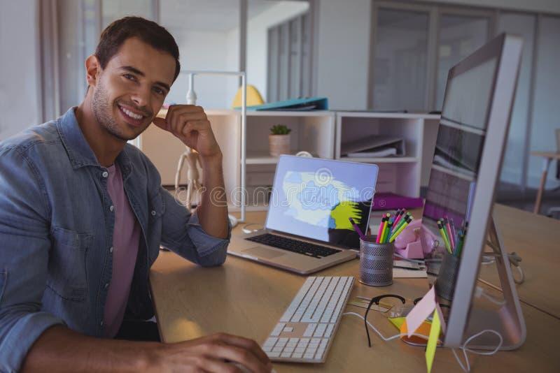 坐在创造性的办公室的微笑的商人画象 免版税库存图片