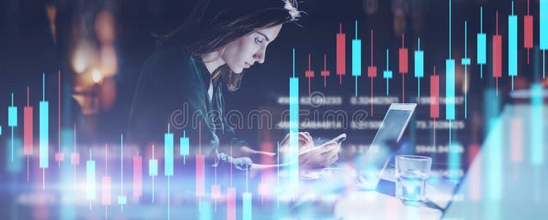 坐在前面手提电脑的夜办公室和使用她的手机的女商人 红色和绿色烛台 库存图片
