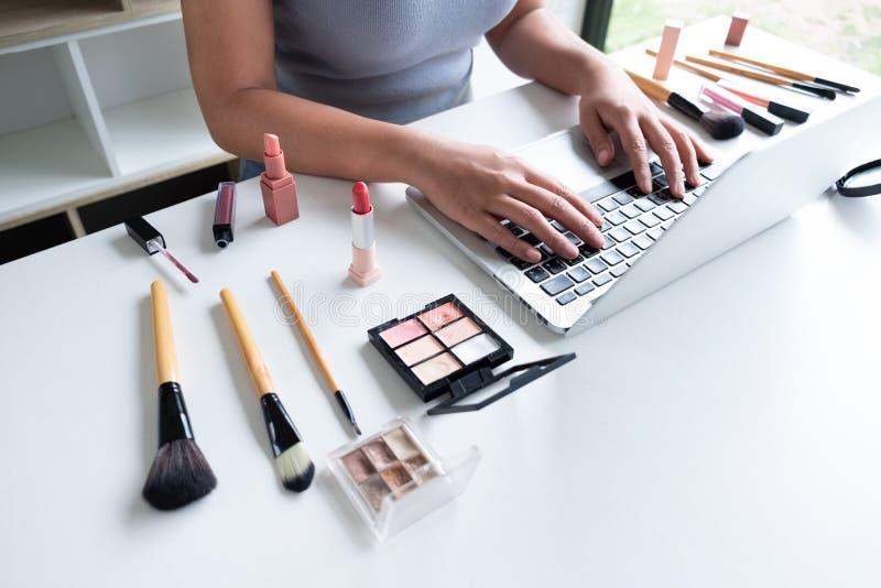 坐在前面片剂的秀丽博客作者当前秀丽化妆用品 美女用途化妆用品回顾在网上补偿 免版税库存照片