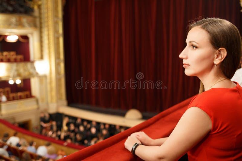 坐在剧院的礼服的年轻微笑的妇女 免版税图库摄影