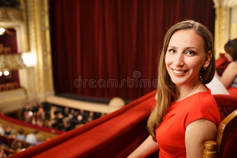 坐在剧院的礼服的年轻微笑的妇女 免版税库存图片