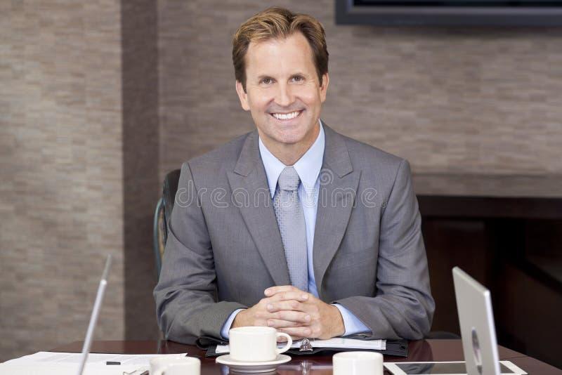坐在办公室会议室里的生意人 免版税图库摄影