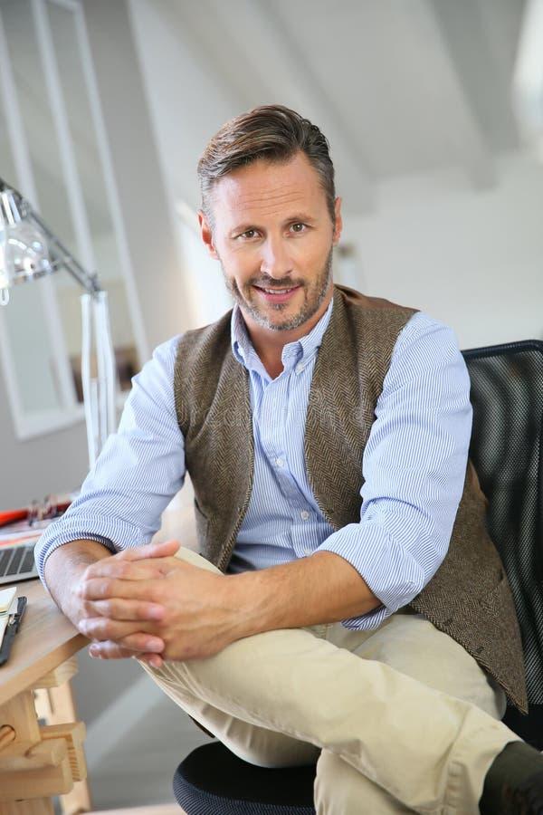 坐在办公室和微笑的英俊的人 免版税库存照片