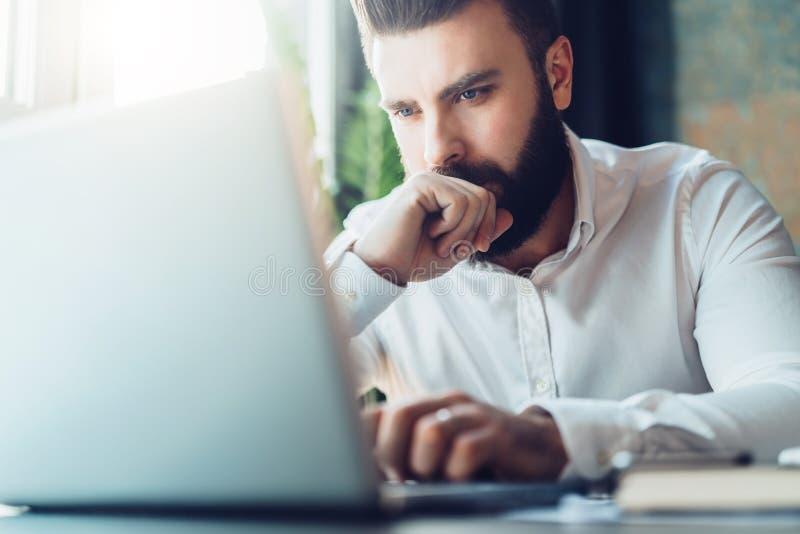 坐在办公室在桌上和使用膝上型计算机的年轻严肃的有胡子的商人 人研究计算机,检查电子邮件 免版税库存图片