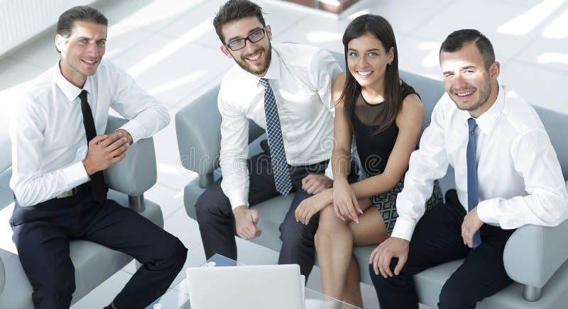 坐在办公室大厅的友好的企业队 库存照片