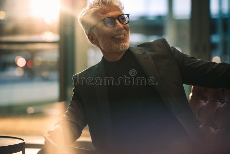坐在办公室大厅的微笑的成熟商人 免版税图库摄影