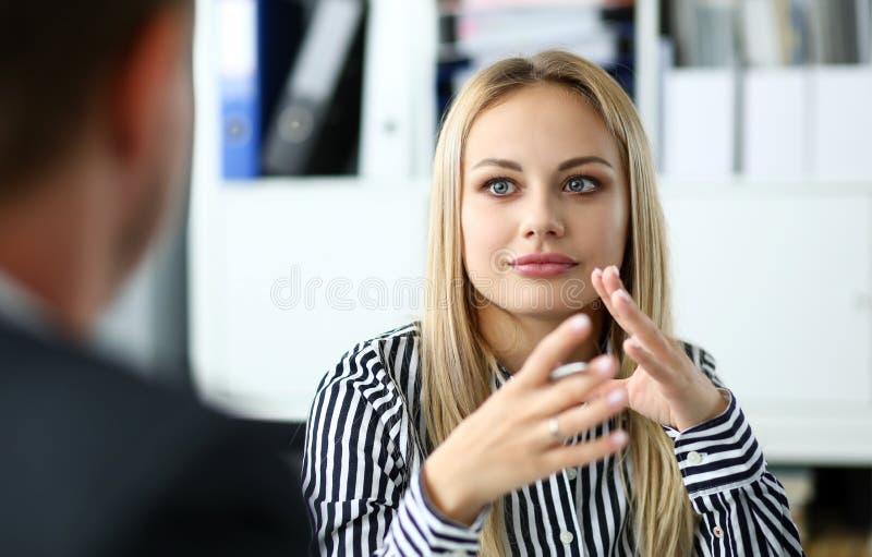 坐在办公室工作场所的美丽的白肤金发的干事 图库摄影