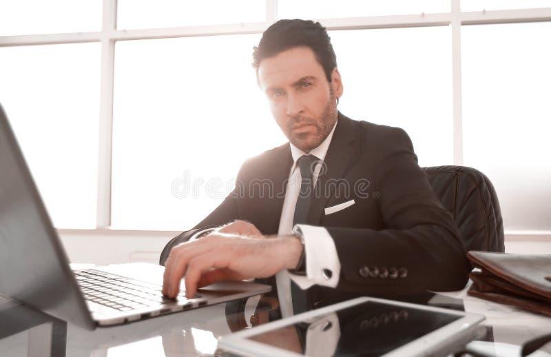 ?? 坐在办公室桌上的负责任的商人 库存照片