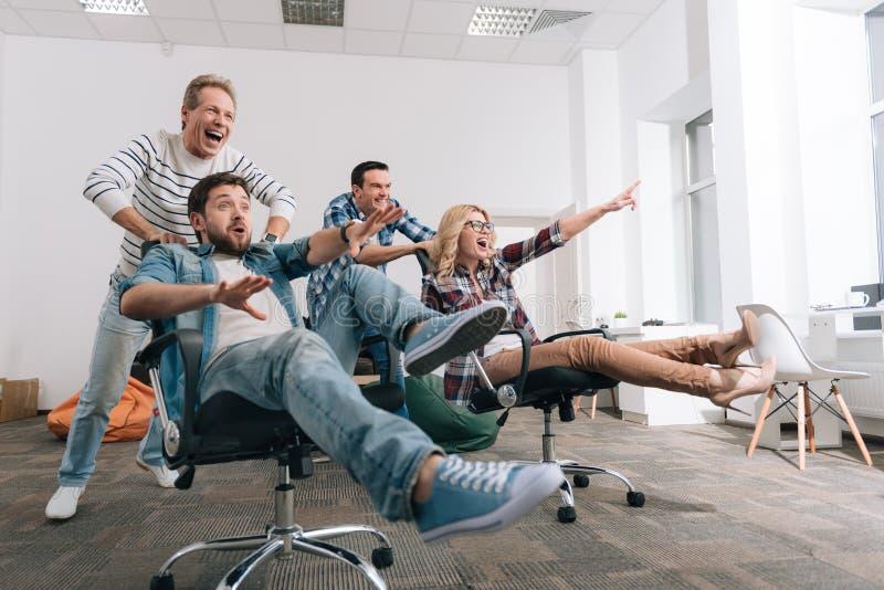 坐在办公室椅子的快乐的愉快的人民 免版税库存照片