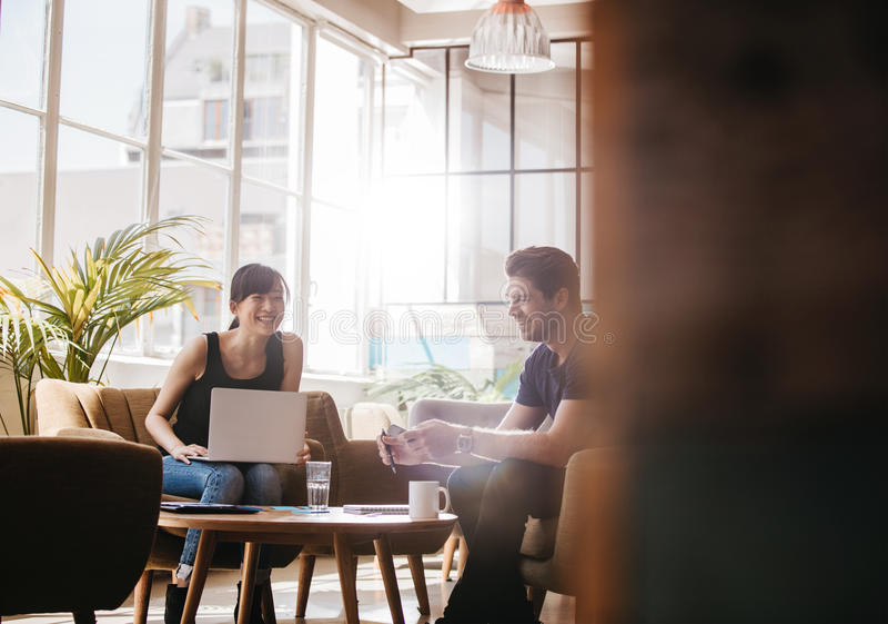坐在办公室的两买卖人游说谈话和微笑 免版税库存照片