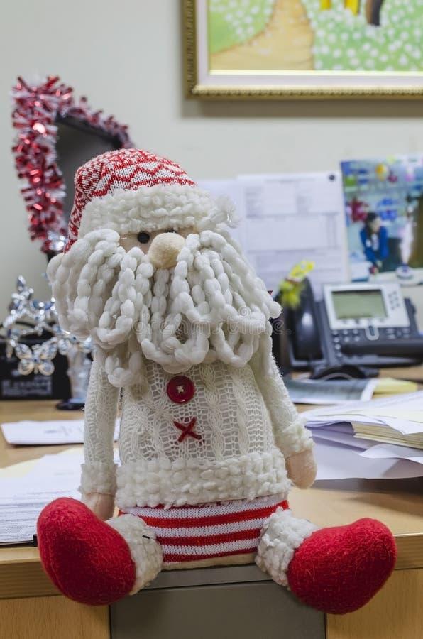 坐在办公室的圣诞老人项目 库存照片