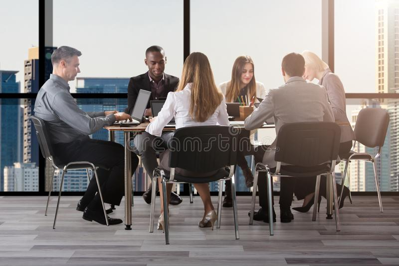 坐在办公室的小组不同的买卖人 免版税图库摄影