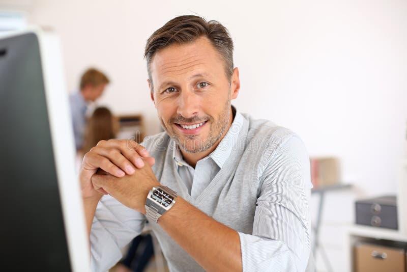 坐在办公室的微笑的成熟人 免版税库存图片