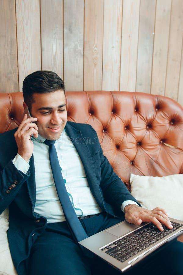 坐在办公室的快乐的商人 库存照片