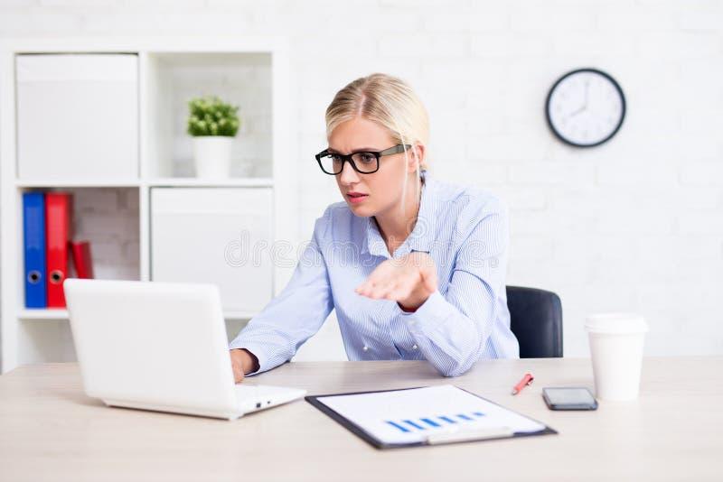坐在办公室的被注重的女商人有c的问题 库存照片