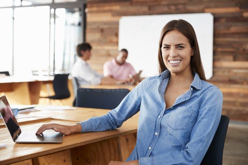 坐在办公室的年轻深色头发的妇女看ï ¿ ½对照相机 库存照片