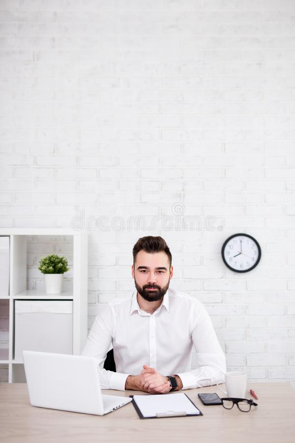 坐在办公室-在白色砖墙的拷贝空间的英俊的有胡子的商人 库存照片