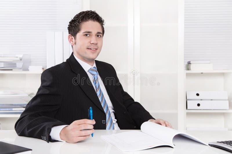 坐在办公室-成功的微笑的经理。 免版税图库摄影