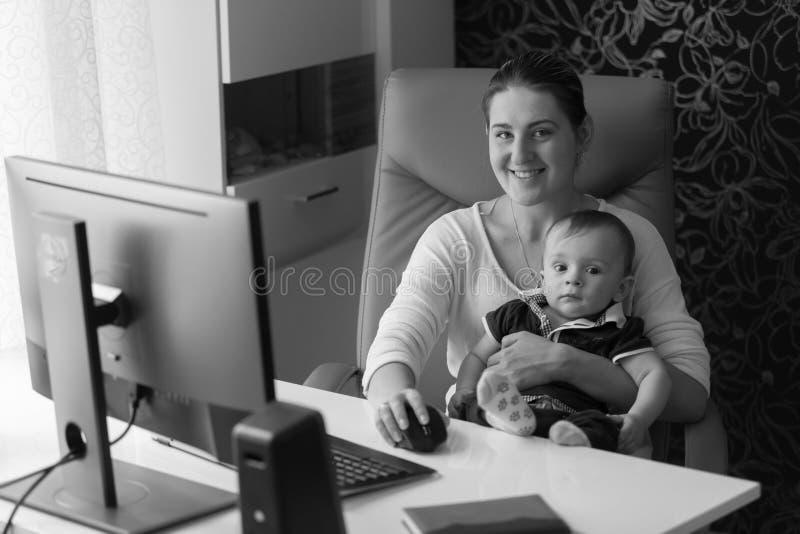 坐在办公室cha的微笑的母亲黑白画象 免版税库存图片
