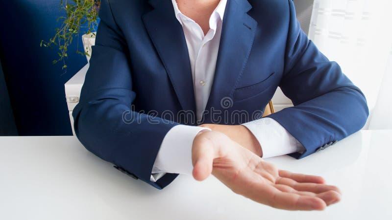 坐在办公桌后的商人的特写镜头图象伸手和请求金钱 库存图片