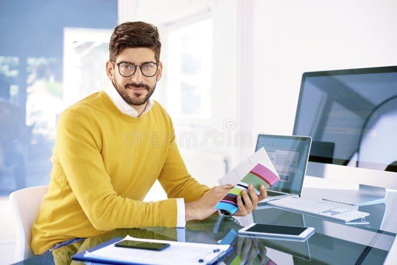 坐在办公桌和工作的商人 免版税库存照片