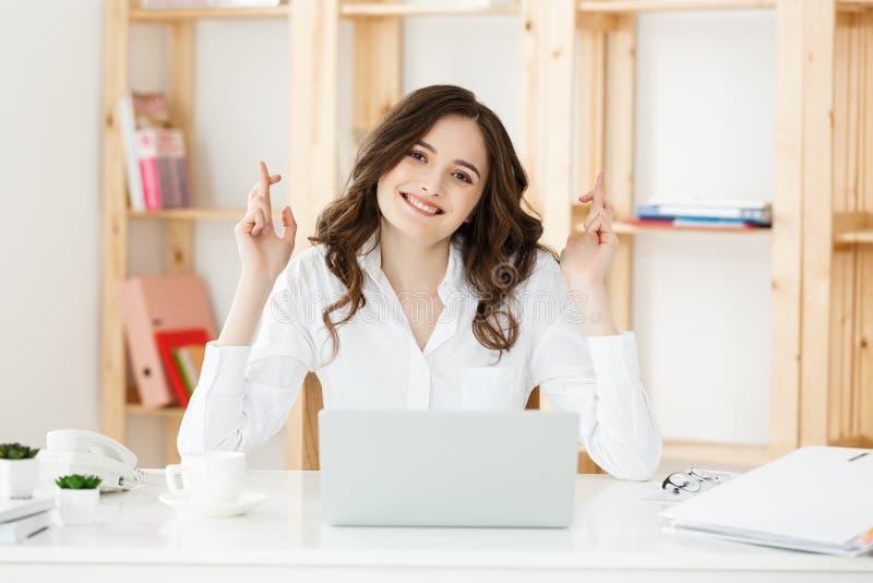 坐在办公桌和握手指的愉快的年轻白种人女商人画象横渡了  免版税库存照片