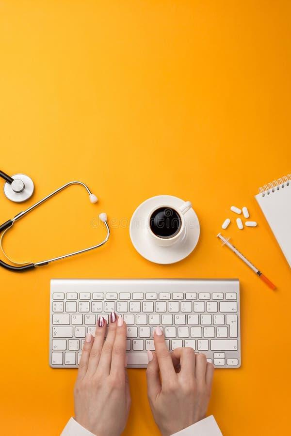 坐在办公桌和研究他的计算机的医生用医疗设备所有,顶视图 免版税库存图片