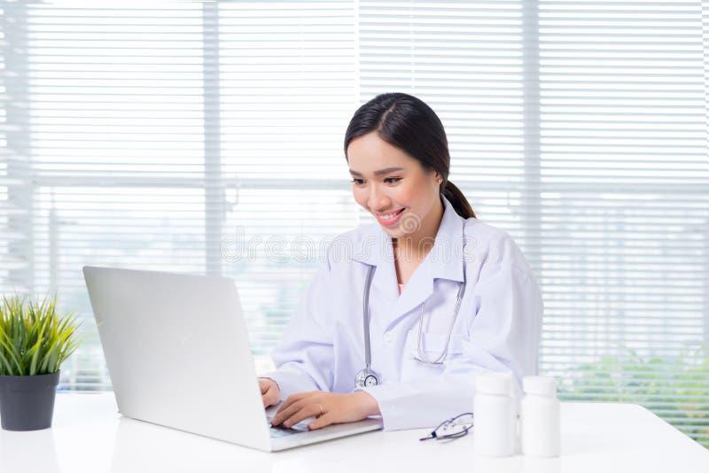 坐在办公桌和运作的w的年轻人微笑的女性医生 免版税库存图片
