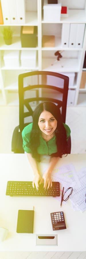 坐在办公桌和键入在键盘的一个女孩的顶视图 图库摄影