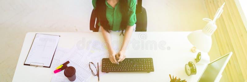 坐在办公桌和键入在键盘的一个女孩的顶视图 库存图片
