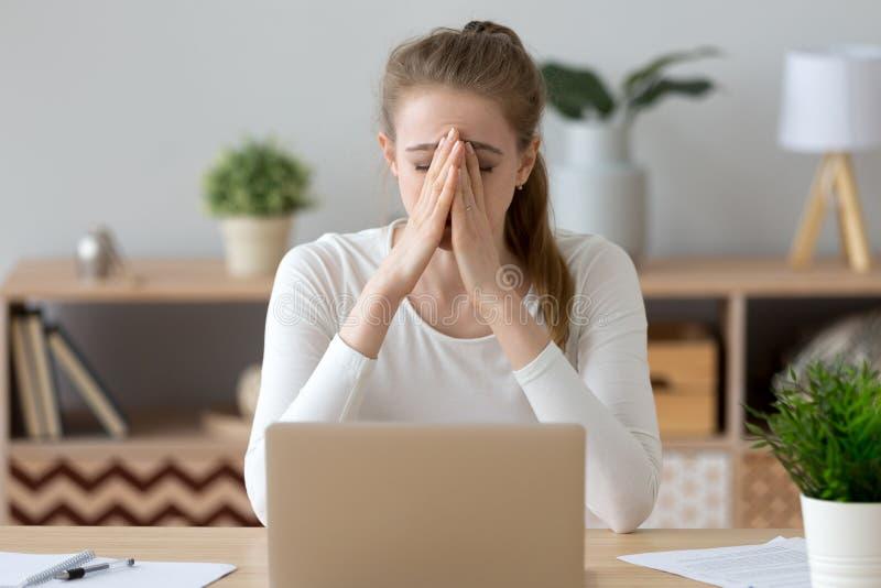 坐在办公桌的工作的沮丧的妇女 免版税图库摄影