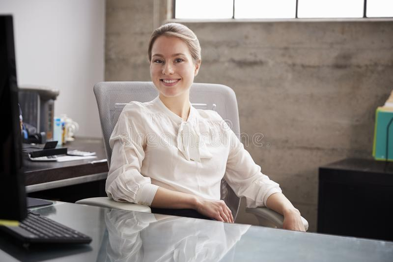 坐在办公桌的年轻白人妇女微笑对照相机 库存照片