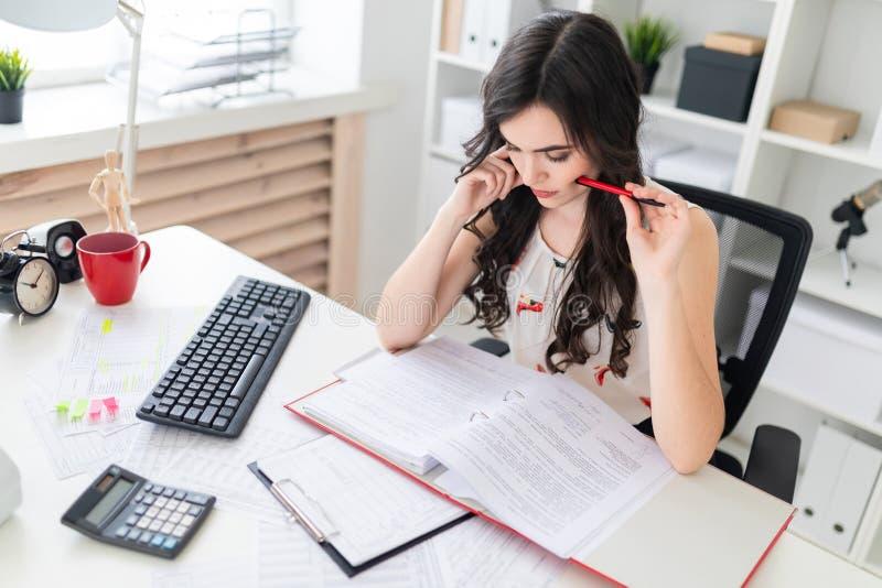 坐在办公桌的美丽的女孩拿着笔在面颊附近和看在与文件的一个文件夹 库存图片