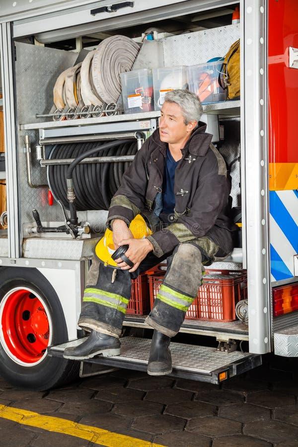 坐在卡车的体贴的消防员 库存照片