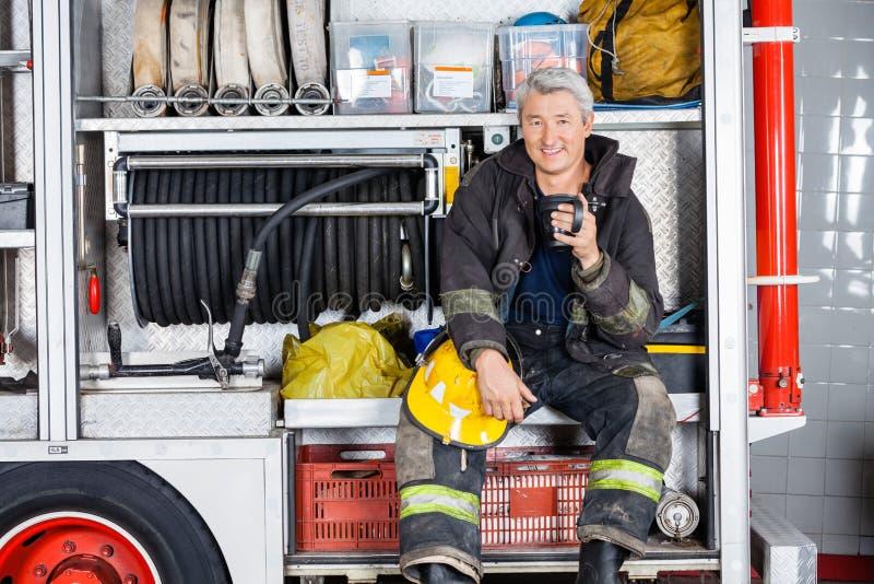 坐在卡车的愉快的消防员在消防局 免版税库存图片