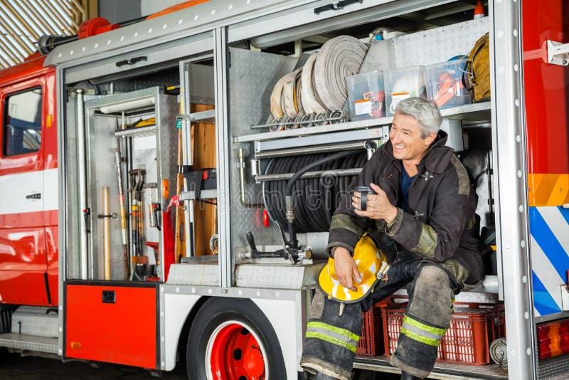 坐在卡车的愉快的消防员在消防局 库存照片