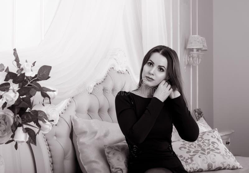 坐在卧室的美丽的年轻深色的妇女画象,投入耳环  免版税库存图片