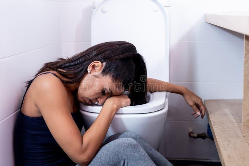 坐在卫生间里的美丽的拉丁妇女遭受感觉绝望哀伤和有罪在饮食失调的厌食善饥癖 免版税库存照片