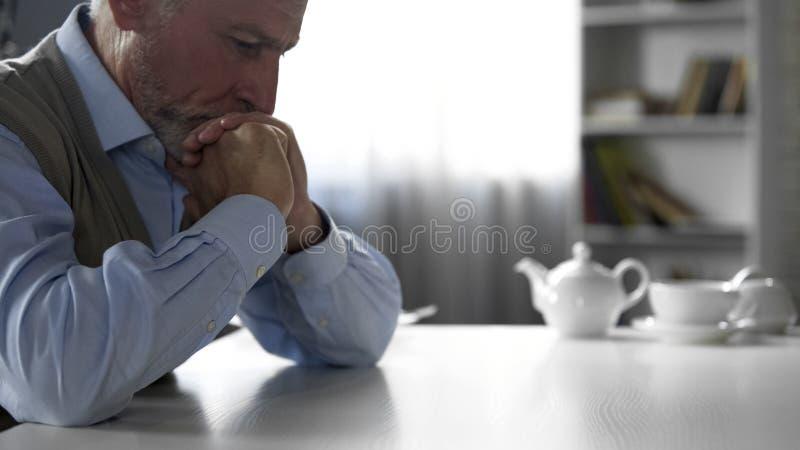 坐在厨房用桌上的年长绅士有坚硬想法,消沉 免版税库存照片