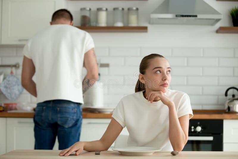 坐在厨房用桌上的懒惰体贴的妻子,当丈夫厨师时 库存照片