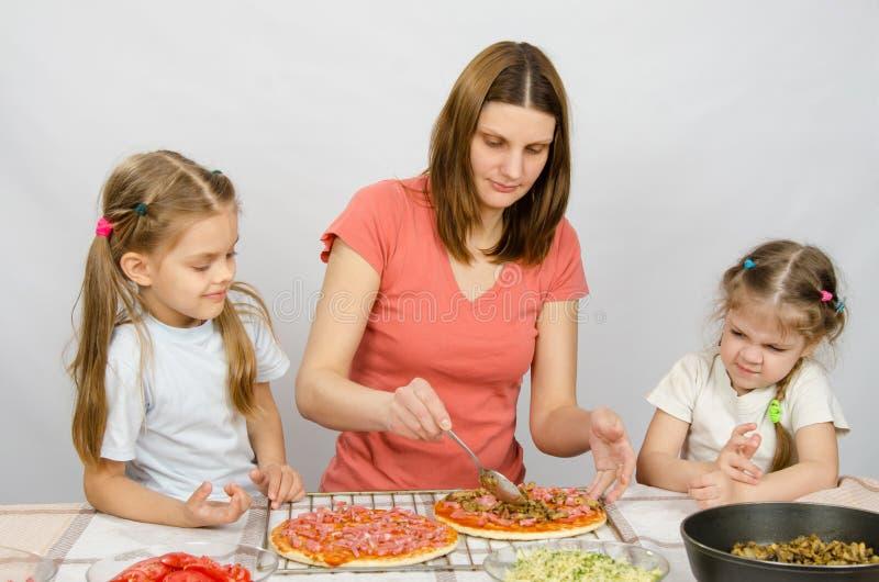 坐在厨房用桌和手表上的两个小女孩作为准备薄饼的母亲 免版税库存照片