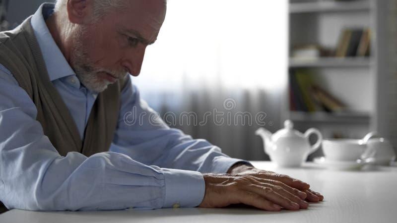 坐在厨房用桌,老男性遭受的寂寞上的孤独的退休人员绅士 免版税库存图片