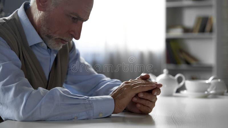 坐在厨房用桌,鳏夫痛苦寂寞上的被抛弃的老绅士 免版税库存照片