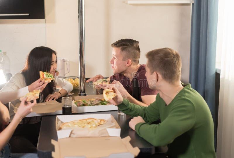 坐在厨房里和吃比萨的四个年轻愉快的朋友公司  免版税库存照片