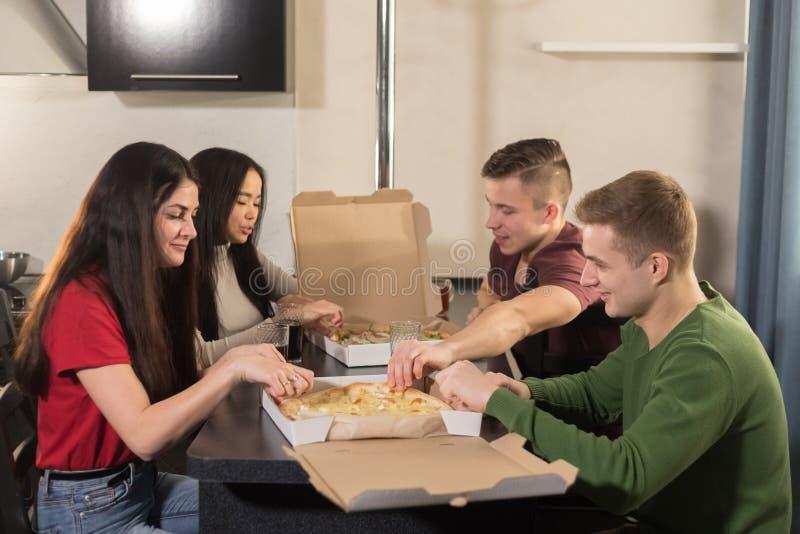 坐在厨房里和打开比萨箱子的四个年轻朋友公司  免版税库存照片