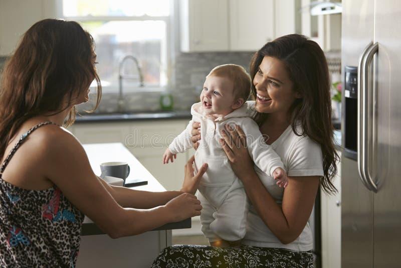 坐在厨房里的女性夫妇拿着他们的女婴 免版税库存照片