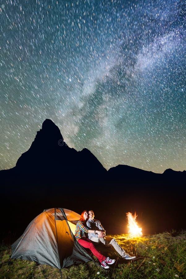 坐在发光的帐篷和营火附近的对远足者,看对在晚上发光在野营的满天星斗的天空 免版税库存图片