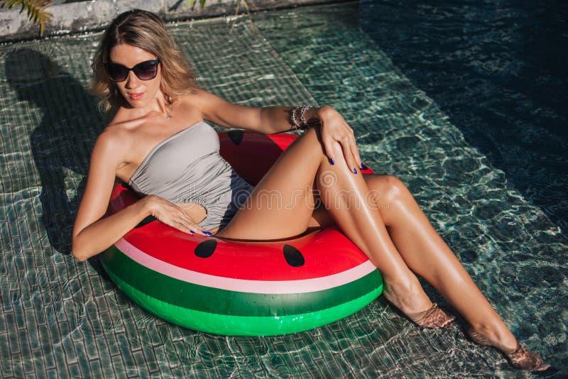 坐在可膨胀的圆环的可爱的年轻女人在游泳池边 免版税库存图片